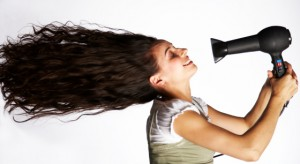 Mid adult woman holding hair dryer in front of face, side view